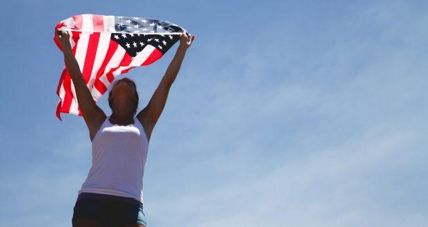 vrouw houdt Amerikaanse vlag vast tijdens road trip