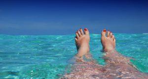 benen en roodgelakte voeten in een azuur blauw zee